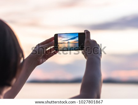 Smartphone camera in tourist woman person'??s hands who taking photo on touch screen of beautiful seascape sky with clouds during sunset at golden happy hour at dawn #1027801867