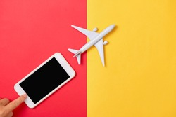 Smartphone cellphone with blank white screen and Model plane on red yellow background.