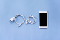 Smartphone, Charger, and Earphones on Blue Background Top View