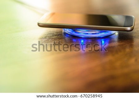 Smartphone charging on a charging pad. Wireless charging #670258945