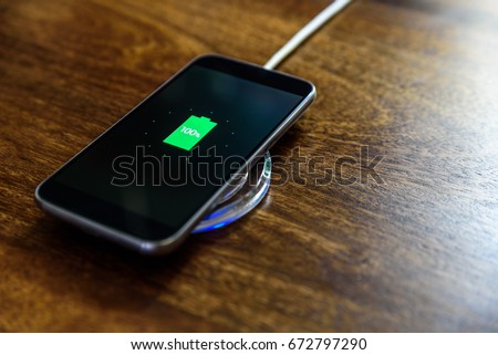 Smartphone charging on a charging pad. Wireless charging #672797290