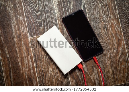 Smartphone charging with power bank on dark wooden surface.