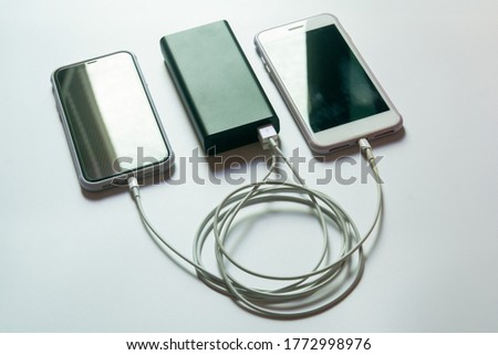 Smartphone charging with power bank on white desk