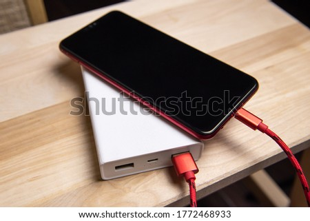 Smartphone charging with power bank on wood board.