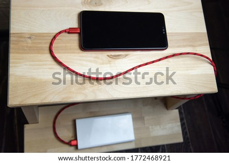 Smartphone charging with power bank on wooden chair.