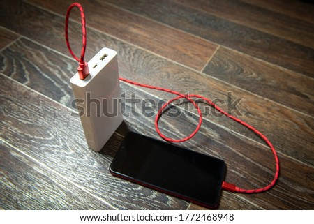 Smartphone charging with power bank on wooden surface.
