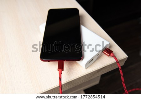 Smartphone charging with power bank on wooden table.