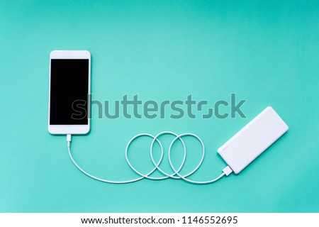 Smartphone Charging with Power Bank through USB Cable on Turquoise Background Top View