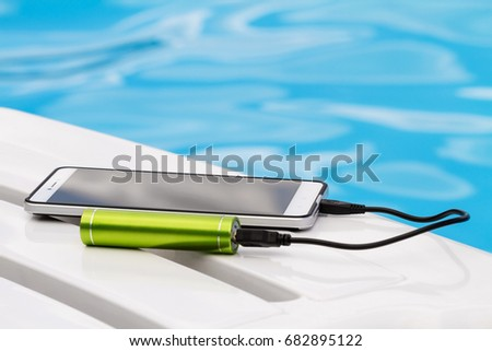 Smartphone connected to the green portable battery charger through USB cable on blue water background. Emergency charging of the phone on a lounger near the swimming pool during the rest. #682895122