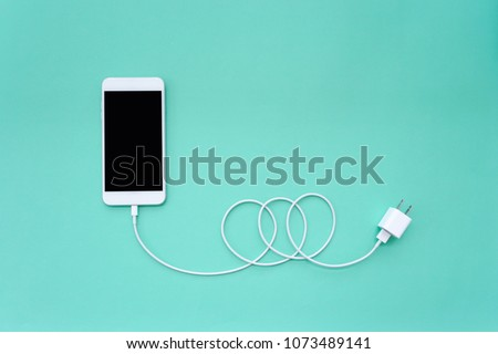 Smartphone Connects to Charger through USB Cable on Turquoise Background Top View Stockfoto ©