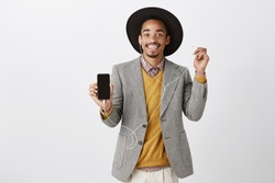 Smartphone definitely worth buying. Portrait of satisfied good-looking african customer in classy suit and hat, showing smartphone, taking off earbud, desctibing good quality of phone and earphones