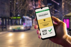 Smartphone displaying a valid digital vaccination certificate for COVID-19 in male's hand, downtown and city bus in background. Vaccination, disease immunity passport, health and surveillance concepts