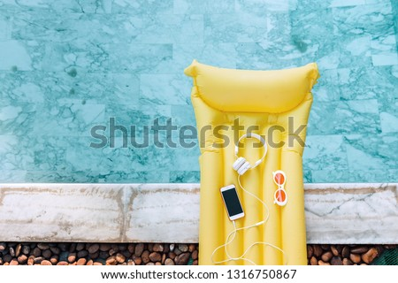 Smartphone, earphones and sunglasses on yellow pool float in blue water, high view from above.