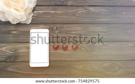 smartphone, flower, heart shape on a wooden background. love. romance