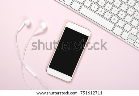 Smartphone, headphones and computer keyboard on pink and blue background. Technology
