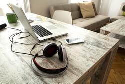 Smartphone, Headphones and Laptop on a wooden Desktop.