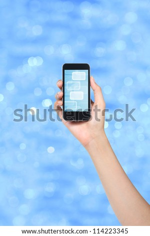 smartphone holded by female hand over blue background