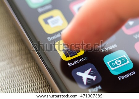 Smartphone home screen, business icon in the focus, finger tip is about to launch application.