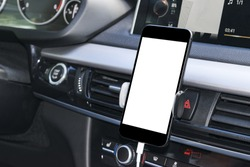 Smartphone in a car use for Navigate or GPS. Driving a car with Smartphone in holder. Mobile phone isolated white screen. Blank empty screen. copy space. Empty space for text. car interior details.