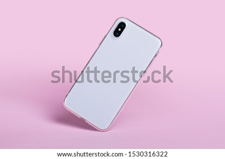 Photo of  Smartphone in clear phone silicone case falls down, back view. iPhone X case mockup isolated on pink background