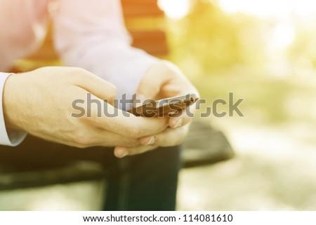 smartphone in hand, blurred background