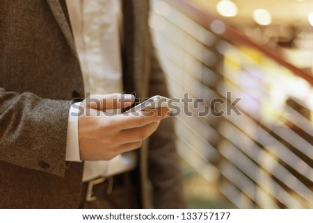 Smartphone in hand of businessman, blurred background, business building interior