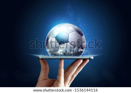 Smartphone in hand with a 3D soccer ball on a blue background. Bets, sports betting, bookmaker. Mixed media.