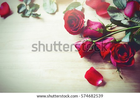 Smartphone in hands with red roses photo on screen with bouquet of roses background.Say love  to your lovers in Valentine's Day. Love is all around loving you all day and night. Love digital concept.