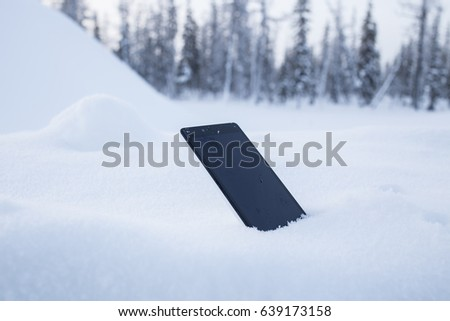 Smartphone in the snow. Use the phone on the nature.