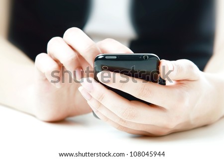Smartphone in woman's hands on white background