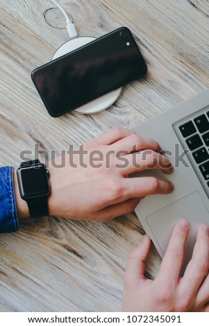 smartphone is charging by wireless charger near man hands with laptop on wooden background #1072345091