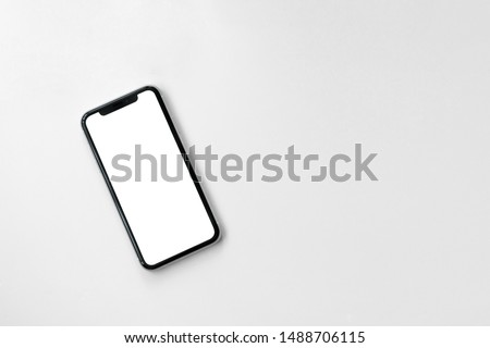 Smartphone lying on surface table or office desk. New modern black frameless smartphone mockup with white screen lying on surface. Isolated on white background.