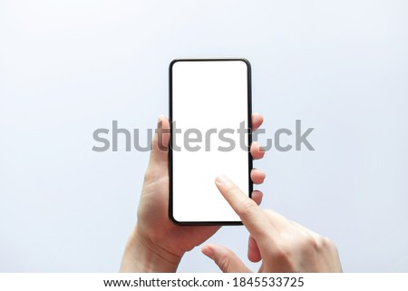 Smartphone mockup. Close up hand holding black phone white screen. Isolated on white background. Mobile phone frameless design concept. ストックフォト ©