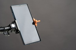 Smartphone on the holder. Smartphone is mounted vertically on the holder. Mobile phone on a gray background. Smartphone with a clear screen. Phone next to the text location. Technical gadgets.