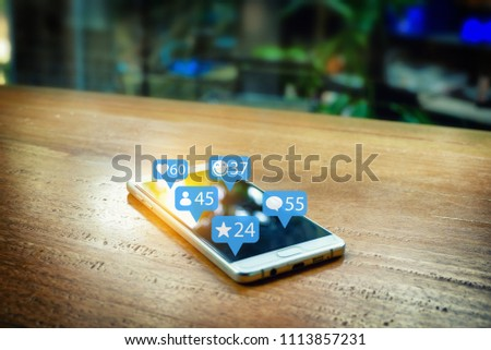 Smartphone on the wooden bar in the coffee shop. And Social Network graphic icon.