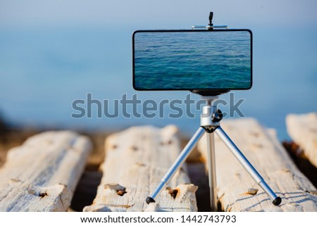 Smartphone on tripod making the pictures of the beautiful water surface