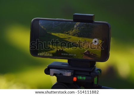 Smartphone on tripod recording timelapse in the sunset with rural mountain landscape background