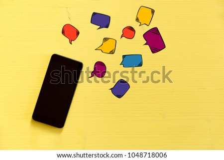 Smartphone on yellow background with text bubbles around. Messaging, texting and connection concept #1048718006