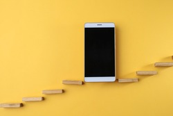 Smartphone on yellow background with wooden sticks forming stairs