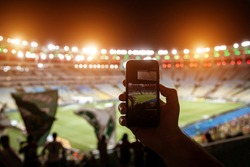 Smartphone photographing football game on the stadium.
