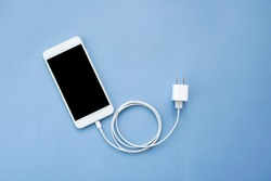 Smartphone Plug In with Charger Adapter on Blue Background Top View