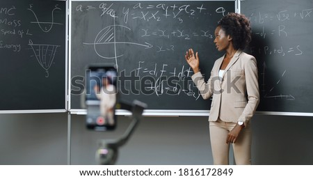 Smartphone recording video lesson at school. African American young female teacher explaining math or physics formulas at class. Online studying.
