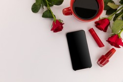 Smartphone, red lipstick, nail varnish, coffee and roses on white background. technology connection romance valentine's day copy space.