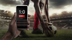 Smartphone screen with mobile app for betting and score. Device with match results on screen, sportsman on background during match. Gambling, betting, sport, finance, modern technologies concept.