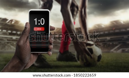 Smartphone screen with mobile app for betting and score. Device with match results on screen, sportsman on background during match. Gambling, betting, sport, finance, modern technologies concept. Foto stock ©