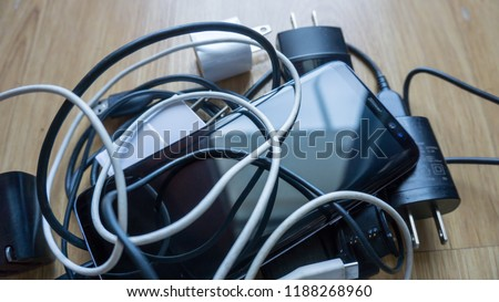 Smartphone tangled in differnt electronics cables chargers usb and black and white wires. Horizontal view #1188268960