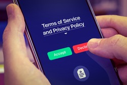 Smartphone user refuses to accept Terms of Service and Privacy Policy mobile app. Dark app interface with Accept and Decline buttons. Finger touches the Decline button