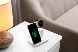 Smartphone, watch and earphones charging on wireless pad in room