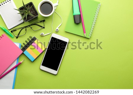 Smartphone. White phone and earphone and notepad, glasses, on a bright green background. top view. space for text #1442082269