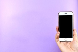 Smartphone with a black screen turned off in hand, on a purple background.